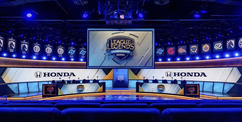 """Picture showing different parts from an League of Legends eSports Tournament. In between you can see the teams, the """"active players"""" position. and some sponsors."""