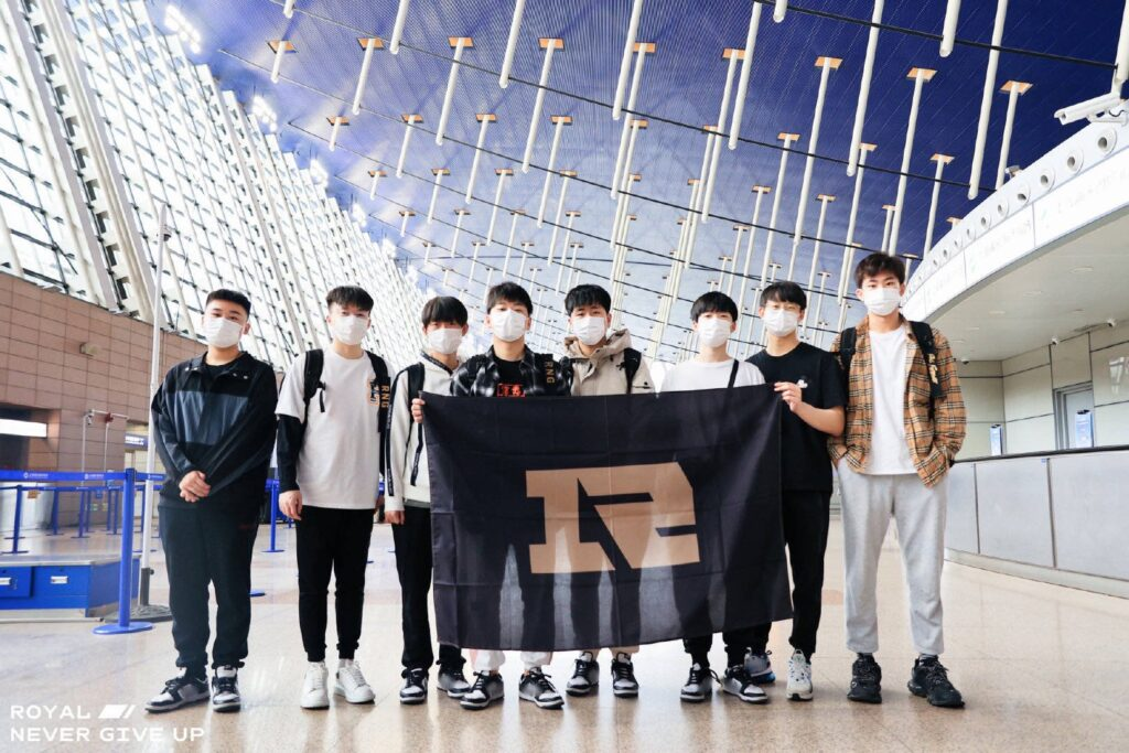 RNG members at the airport carrying their team banner | Riot Games 2021